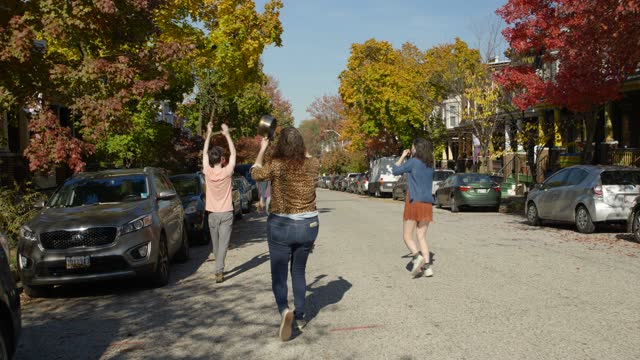 three young people cheer in the street after biden win in baltimore maryland - three people stock videos & royalty-free footage
