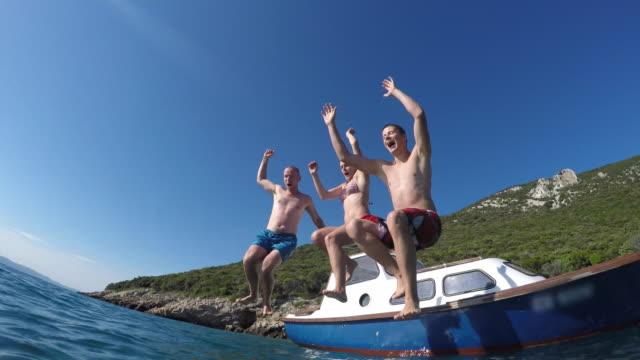 POV drei junge Menschen, die von einem Boot und ins Meer springen
