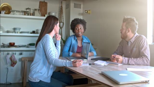 Trois jeunes qui travaillent sur un projet à la maison
