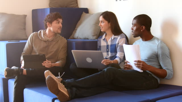 Three young people working together in modern coworking space