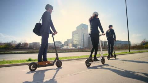 vídeos y material grabado en eventos de stock de slo mo ts tres jóvenes profesionales montando scooters eléctricas en la ciudad bajo el sol - casco herramientas profesionales