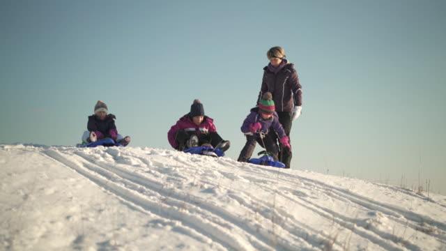 stockvideo's en b-roll-footage met three young sisters on bobsleds - familie met drie kinderen