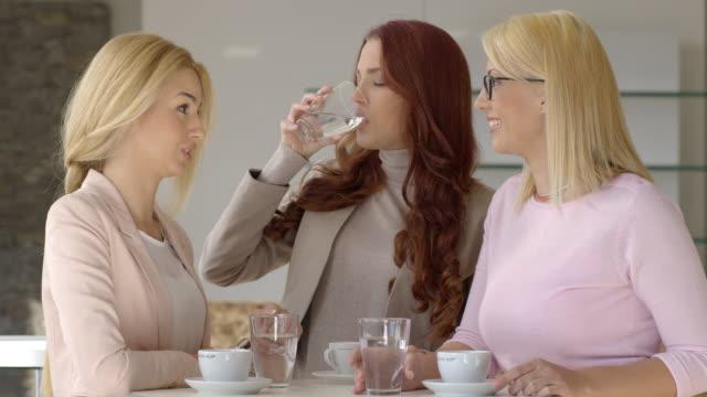 tre unga, framgångsrika, kvinnor i kafé. - endast unga kvinnor bildbanksvideor och videomaterial från bakom kulisserna