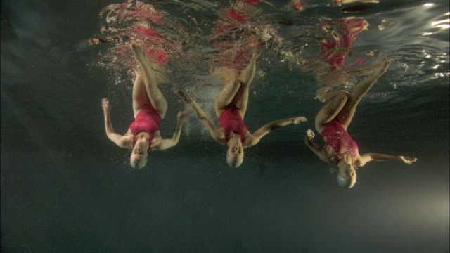 ws, three young synchronized swimmers underwater, basildon, essex, united kingdom - swimming costume stock videos & royalty-free footage
