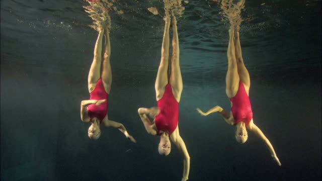 vídeos de stock e filmes b-roll de ws, three young synchronized swimmers underwater, basildon, essex, united kingdom - coordenação