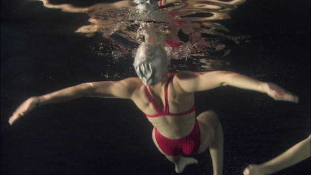 ms, pan, three young synchronized swimmers underwater, basildon, essex, united kingdom - swimming costume stock videos and b-roll footage