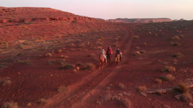 three young teenage and younger siblings navajo native american people riding their horses bareback in the desert near monument valley tribal park at dusk in the summer - utah stock videos & royalty-free footage