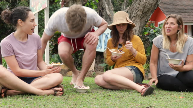three young woman and a young man sitting in the grass eating fruit dishes - hawaiian ethnicity stock videos & royalty-free footage