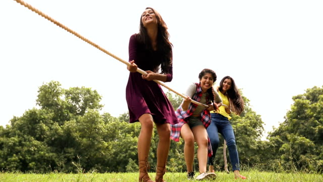 Three young woman playing tug of war in the park, Delhi, India