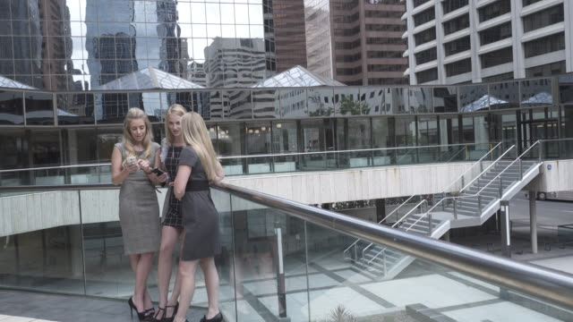 Three young woman share text message in city center