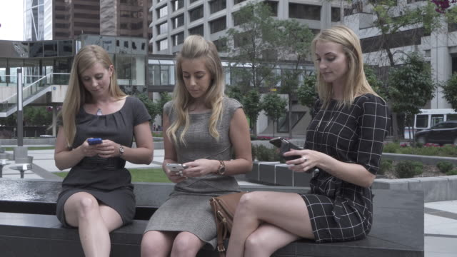 three young woman share text message in city center - long hair stock videos & royalty-free footage