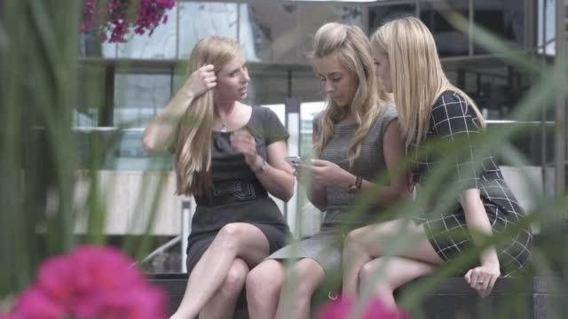 市内中心部の 3 つの若い女性共有テキスト メッセージ - 髪をブラシでとく点の映像素材/bロール