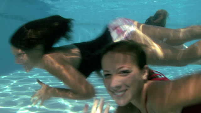 vídeos de stock, filmes e b-roll de three young women and one young man swimming underwater - 14 15 anos