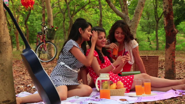 Three young women chatting on a mobile phone, Delhi, India