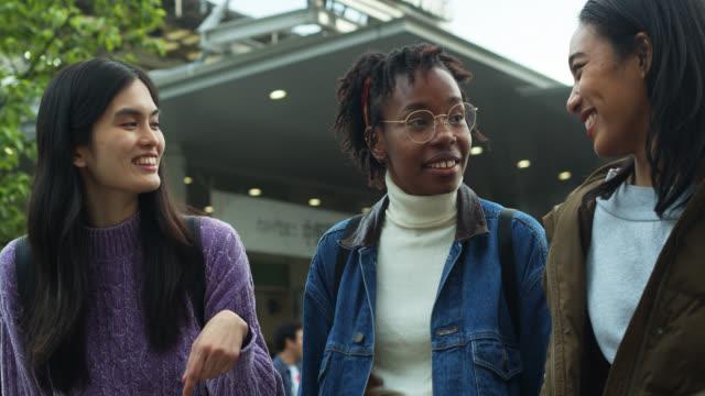 stockvideo's en b-roll-footage met drie jonge vrouwen chatten buiten het station in tokio - mixed race person