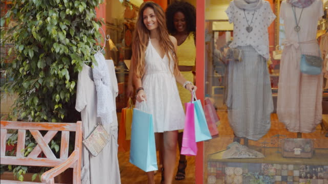Three young women coming out of shop with shopping bags