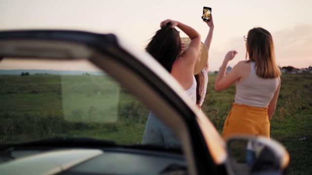 vídeos y material grabado en eventos de stock de three young women dancing next to cabriolet at sunset - cámara en mano