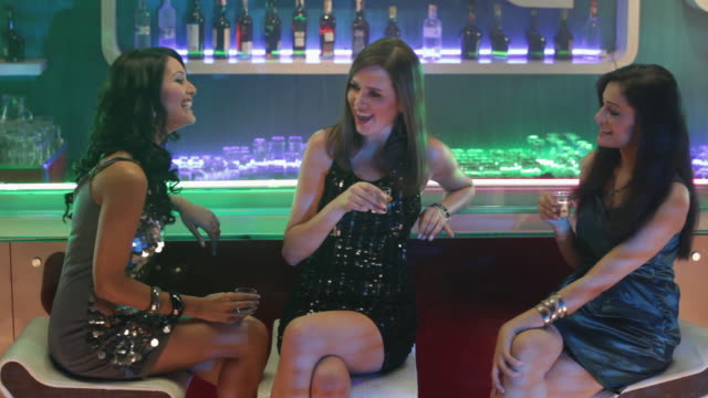 Three young women drinking alcohol at bar counter