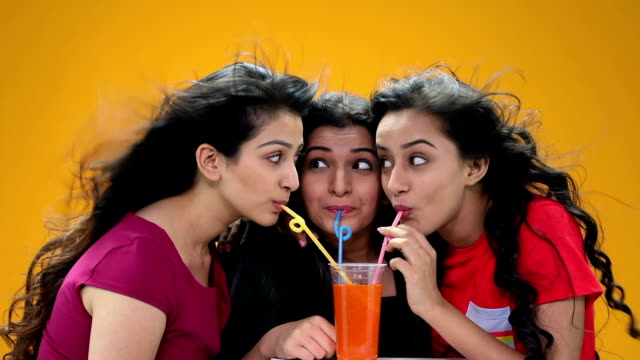 Three young women drinking cold drink