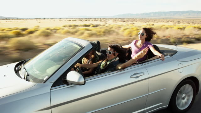 three young women driving along in convertible car - sunglasses stock videos & royalty-free footage