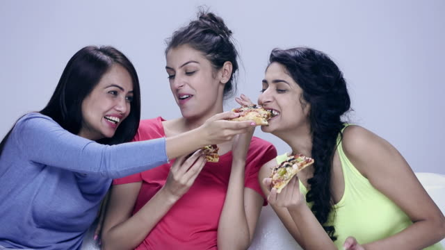 Three young women eating pizza