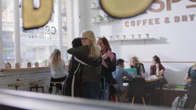 vídeos de stock e filmes b-roll de ws slo mo. three young women embrace and hug in hip downtown coffee shop. - geração millennial