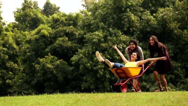 three young women enjoying in the park, delhi, india - wheelbarrow stock videos and b-roll footage