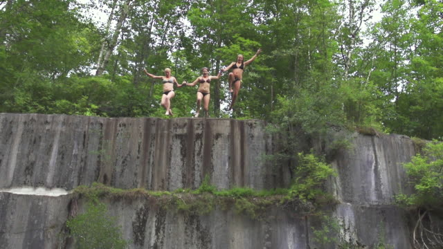 ms td ts slo mo three young women hold hands and jumping off cliff together / dorset, vermont, united states  - cliff stock videos & royalty-free footage