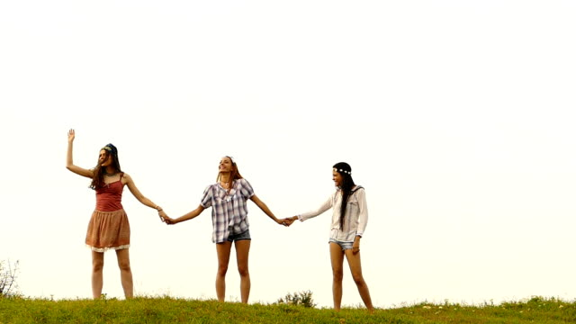 Three young women holding hands and singing,slow motion