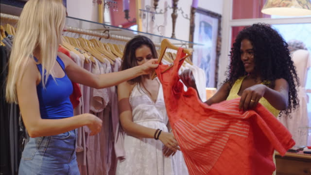 Three young women in shop looking at dresses and clothes
