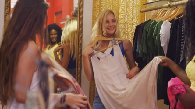 three young women in shop looking at dresses and clothes - anpassen stock-videos und b-roll-filmmaterial