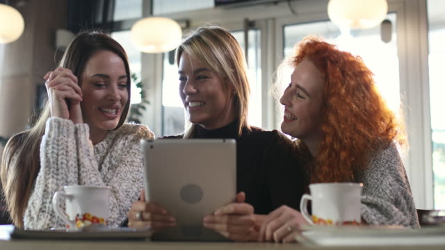 three young women laughing while using digital tablet and communicating in a cafe. - touchpad stock videos & royalty-free footage