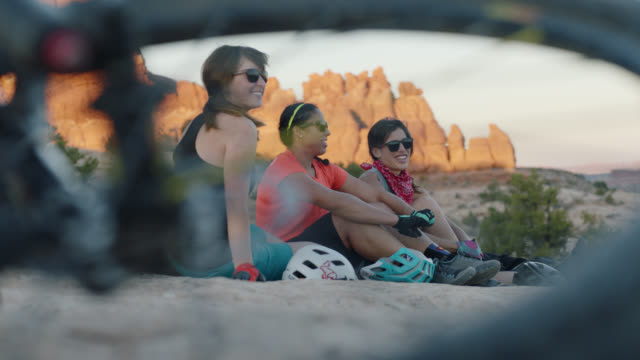 three young women leave mountain bikes to sit and talk on moab trail overlooking scenic sandstone spires. - three people stock videos & royalty-free footage