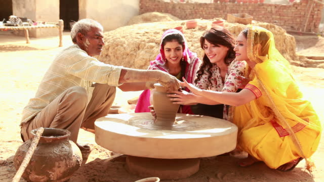 three young women making pot with a potter on a pottery wheel, haryana, india - haryana stock-videos und b-roll-filmmaterial