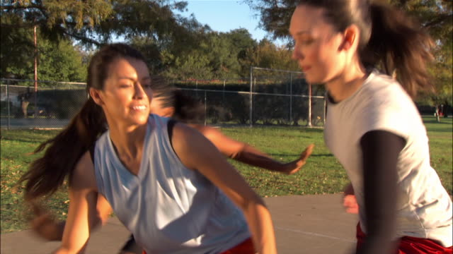 Three young women playing basketball outdoors