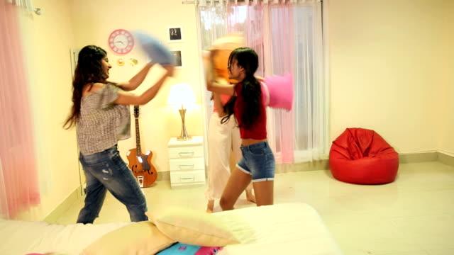 vídeos y material grabado en eventos de stock de three young women playing pillow fight at home, delhi, india - lucha con almohada