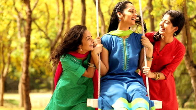 ms three young women playing swing in park / delhi, india - drei personen stock-videos und b-roll-filmmaterial