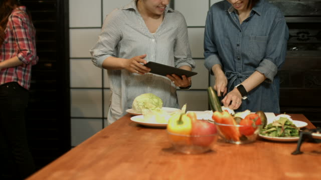 stockvideo's en b-roll-footage met drie jonge vrouwen bereiden van voedsel in de keuken - rijp voedselbereiding