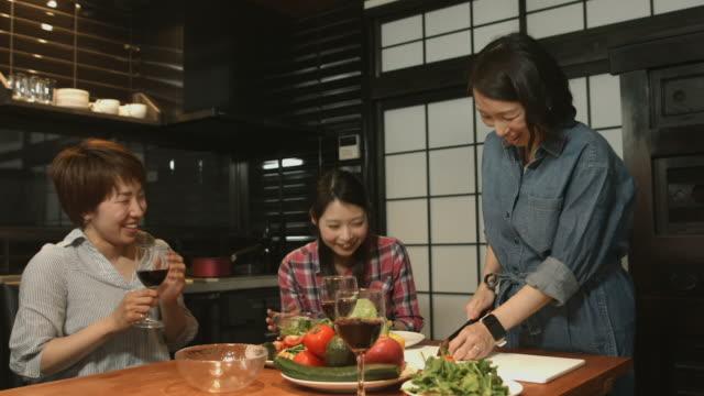キッチンで食事を準備する 3 人の若い女性 - アルコール飲料点の映像素材/bロール