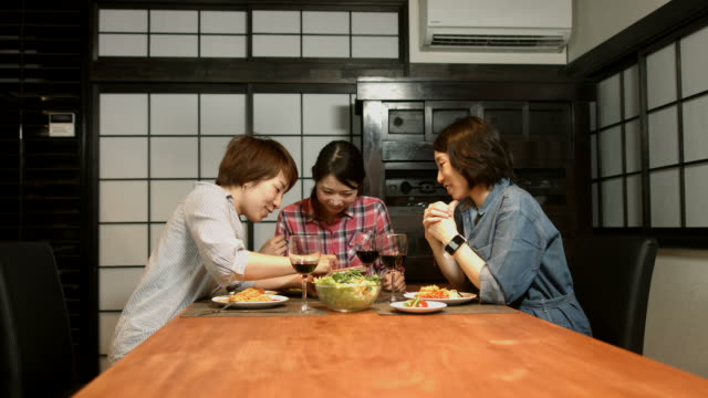 Three young women preparing food in the kitchen