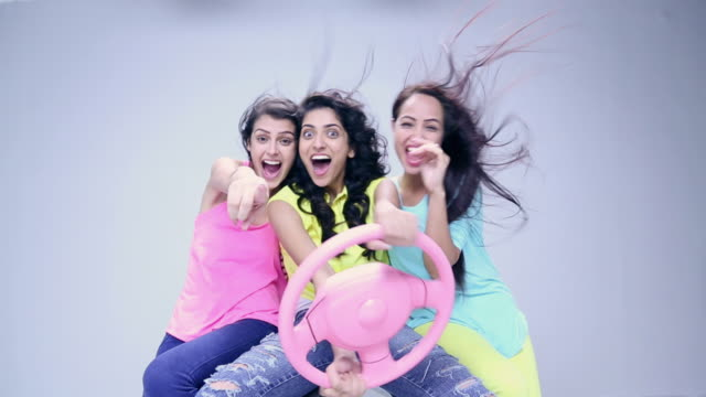 Three young women pretending to driving