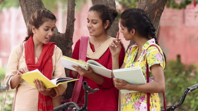 Three young women reading books, Haryana, India