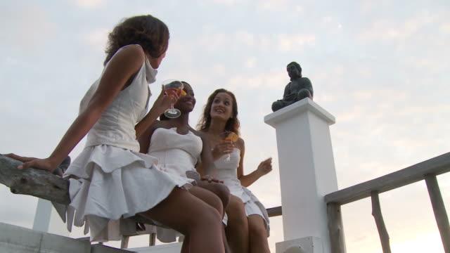 vídeos de stock e filmes b-roll de ms la three young women relaxing on patio  / seychelles - articulação humana