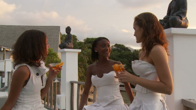 MS Three young women relaxing on patio  / Seychelles