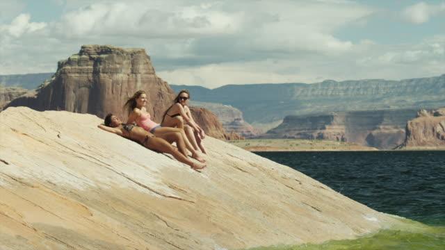 WS Three young women relaxing on rock near Lake Powell / Utah, USA
