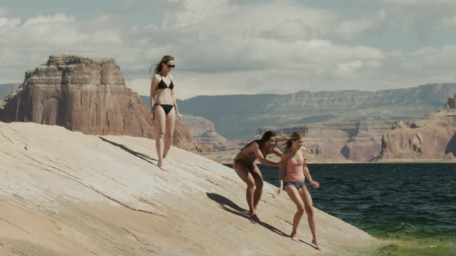 ws three young women relaxing on rock near lake powell / utah, usa - lake powell stock videos and b-roll footage