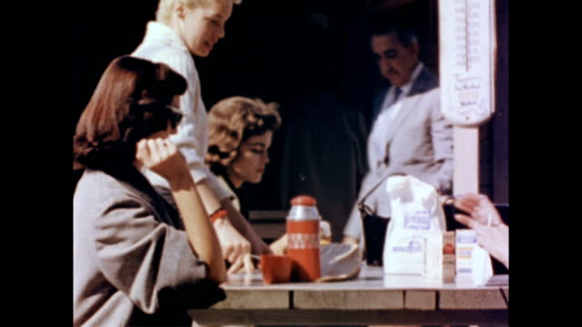 Three young women seated around an outdoor picnic table / another girl sits down to join them as they eat out of paper bags / woman with scarf over...