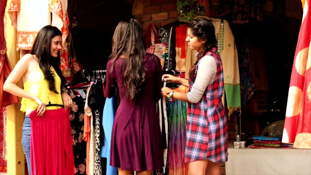 Three young women shopping in the market, Delhi, India
