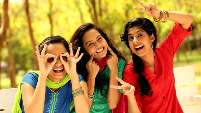 MS Three young women showing hand signs and enjoying in park / Delhi, India