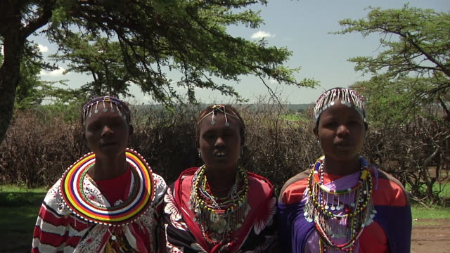 MS Three young women singing and dancing traditional Masai tribal dance / Nairobi, Masai Mara National Reserve, Kenya